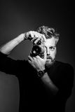 Young bearded man holding retro camera. Against black background. Confident photographer shooting at his studio. Black and white photography stock photos