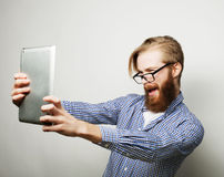 Young bearded man holding tablet Royalty Free Stock Images