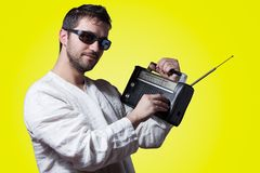 Young bearded man holding a vintage radio. On yellow background Royalty Free Stock Image