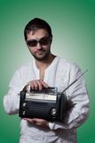 Young bearded man holding a vintage radio. On green background Stock Photography