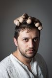 Young bearded man with a huge mock hand on his head. On dark background Stock Photo