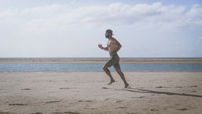 Young bearded man jogging on the sea shore at sunrise. Side portrait of healthy young bearded man running at the beach. With bright sunlight Royalty Free Stock Photo