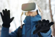 Young bearded man in knitted hat, warm jacket and gloves using virtual reality glasses in winter forest. Future technology concept royalty free stock image