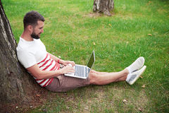 Young bearded man with laptop in the garden Stock Images