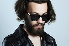 Young bearded man in a leather. Hipster in sunglasses Royalty Free Stock Photo
