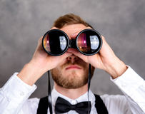 Young bearded man looking through a binoculars Stock Photography