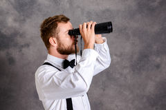Young bearded man looking through a binoculars Royalty Free Stock Photography