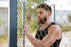 Young bearded man looking through metal urban fence. Close up portrait of young bearded man looking through metal urban fence outdoors Stock Image