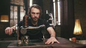 The young, bearded man, makes leather goods stock video