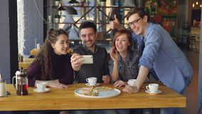 Young bearded man is making video call from pizza house together with best friends. Playful mates are talking, smiling stock footage
