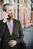 Young bearded man with mobile, outdoor Royalty Free Stock Photos