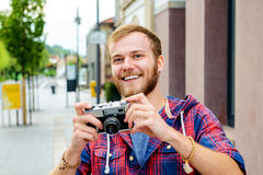 Young bearded man with old camera Stock Images