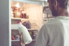 Young bearded man opens the bottle of milk standing near fridge at home stock images