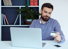 Young bearded man pays by credit card online shopping Stock Images