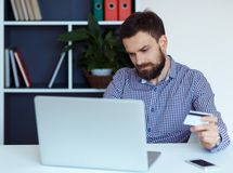 Young bearded man pays by credit card online shopping Royalty Free Stock Photos