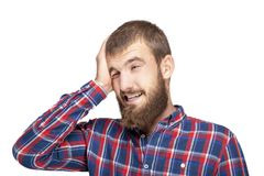 A young bearded man in a plaid shirt is experiencing an annoying mistake or oversight. Emotional portrait on a white background Stock Photo