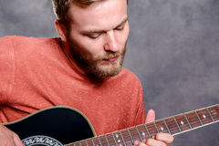 Young bearded man playing acoustic guitar Royalty Free Stock Photo
