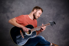 Young bearded man playing acoustic guitar Stock Image