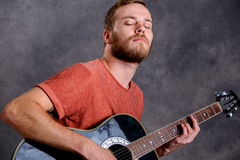 Young bearded man playing acoustic guitar Royalty Free Stock Image