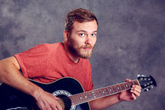 Young bearded man playing acoustic guitar Royalty Free Stock Images