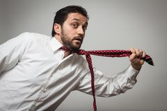 Young bearded man with tie pulling himself. Young bearded man with red tie pulling himself on grey background Stock Image