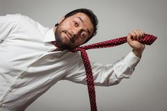 Young bearded man with tie pulling himself. Young bearded man with red tie pulling himself on grey background Stock Photos