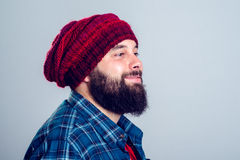 Young bearded man with red woolen cap Royalty Free Stock Photos