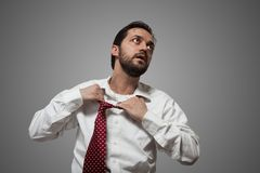 Young bearded man with red tie. Young bearded man removing his red tie on grey background Royalty Free Stock Photo