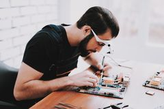 Young Bearded Man Repairing Motherboard from PC. stock image