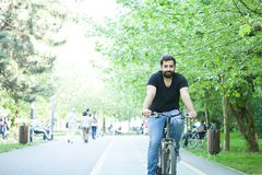 Young bearded man riding a bicycle in the park. In summer Stock Photography