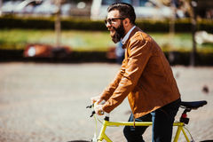 Young bearded man riding on his bicycle outdoors on sunny street Royalty Free Stock Images