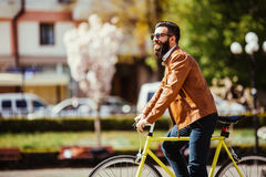 Young bearded man riding on his bicycle outdoors on sunny street Stock Images