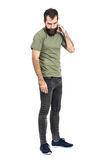 Young bearded man scratching head looking down side view Royalty Free Stock Photography
