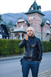 Young bearded  man sending kisses on background of  Beautiful old pink  house in the mountain Royalty Free Stock Photography