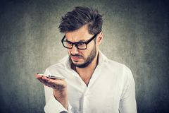 Young bearded man in shirt holding smartphone being upset with voice command function stock photo