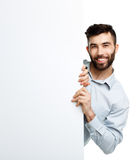 A young bearded man showing blank signboard, isolated over white Stock Photo