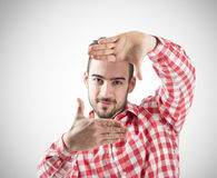 Young bearded man showing finger frame looking at camera Stock Photography