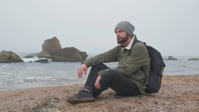 Young bearded man sits alone on beach in the evening and throws pebbles into the water. A young and bearded man sits alone on a rocky beach in the evening and stock video footage