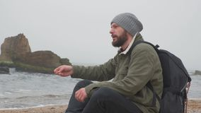 Young bearded man sits alone on beach in the evening and throws pebbles into the water. A young and bearded man sits alone on a rocky beach in the evening and stock footage