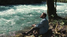 A young bearded man sat down beside a lonely tree and a river to rest. A young and bearded man sits near the stream of water, a fast river refreshes a gentleman stock video