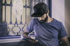 Young bearded man sitting in cafe and using smartphone for texting message. Horizontal. Blurred background. Royalty Free Stock Photos