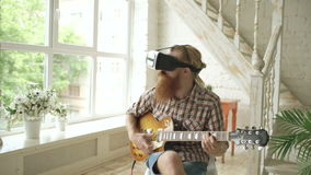 Young bearded man sitting on chair learning to play guitar using VR 360 headset and feels him guitarist at concert at
