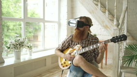 Young bearded man sitting on chair learning to play guitar using VR 360 headset and feels him guitarist at concert at. Young bearded man sit on chair learning to stock video