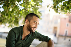 Young bearded man sitting outdoors under trees and smiling. While looking away stock photo