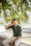 Young bearded man sitting outdoors under trees and smiling Royalty Free Stock Photography