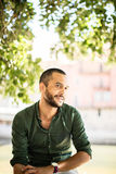 Young bearded man sitting outdoors under trees and smiling Royalty Free Stock Photo