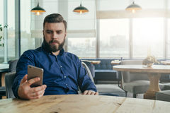 Young bearded man is sitting at table in restaurant and is using smartphone.Man looks at phone screen. Guy using gadget,shopping online,working,blogging,reading Stock Images