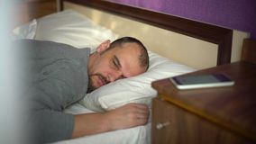Young bearded man sleeping in bed is awaked by alarm signal on his phone