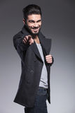 Young bearded man is smiling and pointing his finger Stock Photography