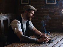 A young bearded man smoking a cigar in a pub Stock Images